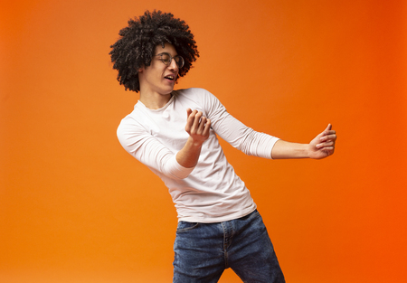 Modern dance. Flexible millennial black guy dancing on orange background
