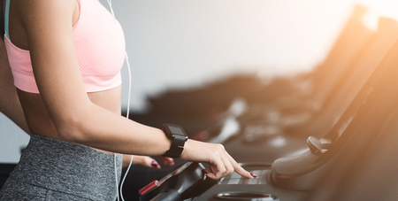 Adjusting speed. Woman training on treadmill, doing cardio workout in gym, crop Stockfoto