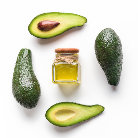 Avocado and oil in jar on white background top view. Organic cosmetic concept