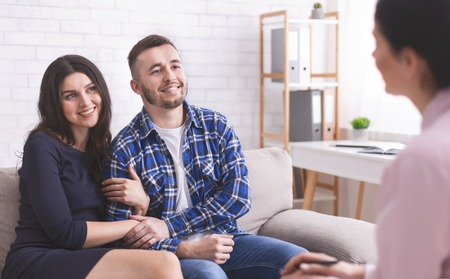 Young cheerful millennial couple at consultation with personal psychologist, free space Stock Photo - 122403885