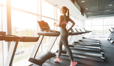 Young woman doing cardio training on treadmill near panoramic window in gym