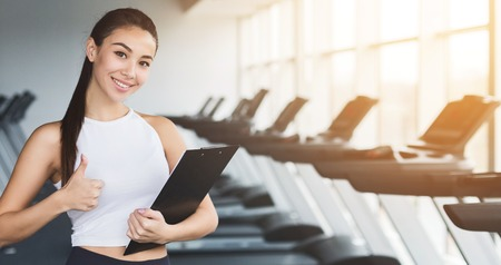 Fitness instructor. Woman with clipboard showing thumb up in gym, copy space