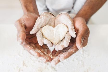 Manos de afro mans sosteniendo las manos de los niños con pasteles en forma de corazón. Concepto de infancia feliz
