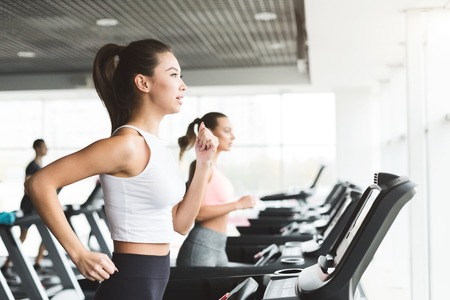 Asian girl working out on treadmill at the gym, side view, copy space Stockfoto