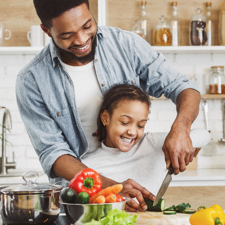 Afro ameriacan father teaching his little daughter to cut vegetables, cooking salad