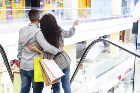 Couple Going Down By Escalator, Holding Shopping Bags, Back View, Copy Space