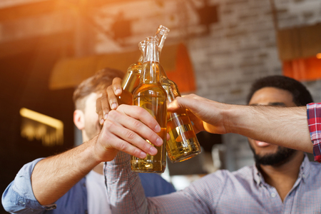 Male Friends Drinking Beer And Clinking Bottles At Bar, Closeup Imagens - 122605406
