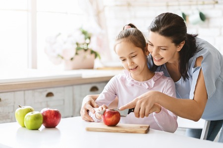 Happy family. Mom Teaching Cute Girl To Cut Apple With Knife. First lesson and healthy lifestyle concept, free space
