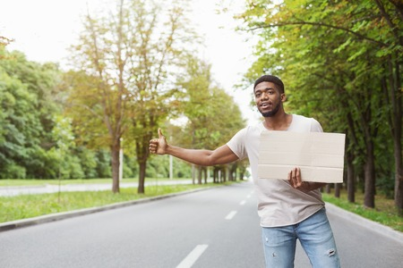 Young afro man with cardboard hitchhiking on road, copy space
