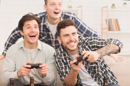 Gamers. Happy Friends Playing Video Games, Having Fun At Home