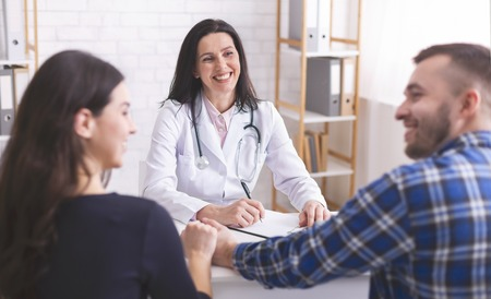 Great news for you! Cheerful doctor consulting young couple during appointment at clinic