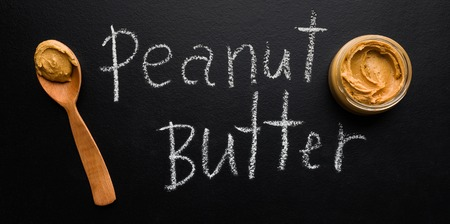 Peanut butter in jar and spoon and text Peanut Butter on concrete background, top view. Organic peanut butter concept