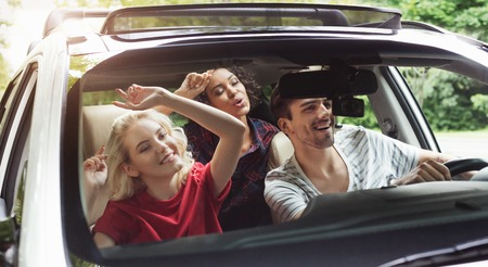 Happy young friends traveling by car, listening to music and singing, having fun Archivio Fotografico