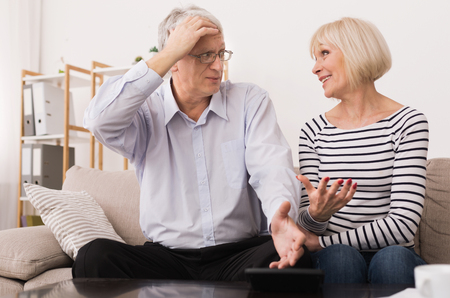 Mature Couple Calculating Bills, Discussing Home Economics In Living Room Foto de archivo
