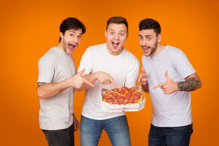 Yummy! Mates Pointing On Pizza And Looking At Camera Over Orange Background 免版税图像