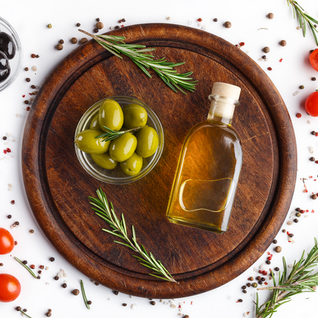 Fresh olives and the oil in bottle with rosemary on board over white background with scattered tomatoes and spicies, top view