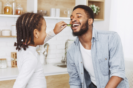 Young daughter is feeding her father with chocolate cookies Archivio Fotografico