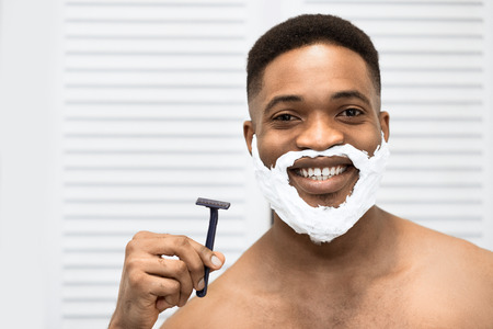 Smiling afro man with torso and shaving foam on his beard, holding razor, looking in mirror at bathroom. Comfort shaving concept, copy space
