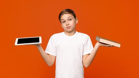 Old school vs new school. Teenage kid choose between Tablet and Book, orange studio background