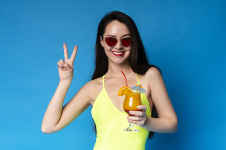 Lovely Summer Girl In Swimsuit Enjoying Cocktail and Showing Peace Gesture, blue studio background Stockfoto