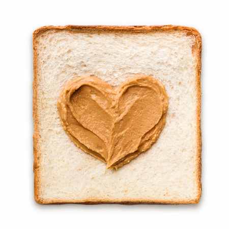 Peanut butter spread in a heart shape on a piece of toast, top view