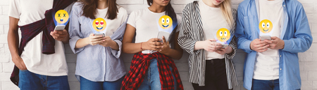 Social networks. Students sending emojis, texting on their smartphones