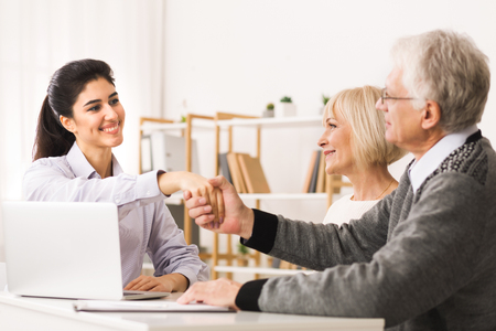 Purchase Deal. Happy Mature Couple Sealing Contract With Financial Advisor, Shaking Hands 版權商用圖片