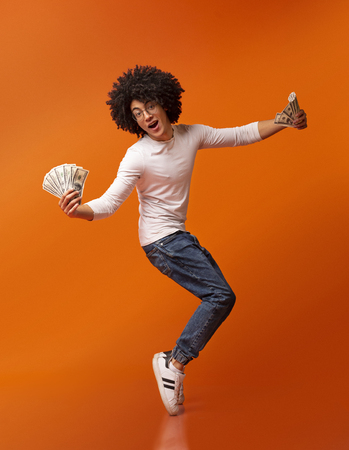 Young and rich. Happy african american guy dancing on tiptoes with money fans, orange studio background Stock Photo