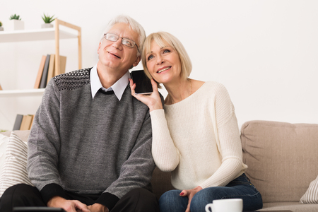 Talking With Relatives. Senior Couple Sharing Smartphone, Having Phone Call