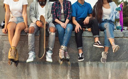 Teen entertainment. Active diverse friends sitting in urban skatepark with skateboards, free space