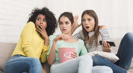 Girls watching horror movie on tv and eating popcorn at home