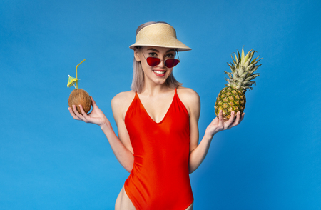 Cute Chick Enjoying Summer Vacation At Tropics, Holding Coconut Cocktail and Fresh Pineapple, blue studio background Stockfoto