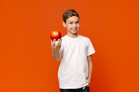 Positive little boy offering fresh red apple on camera, orange studio background 版權商用圖片