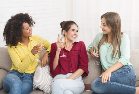 Girlfriends drinking sparkling wine, spending evening together, having slumber party at home
