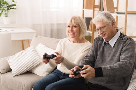 Having Fun. Senior Couple Playing Video Games At Home