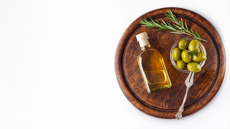 Olive oil and green olives in bowl on wooden board over white background, top view, copy space 写真素材