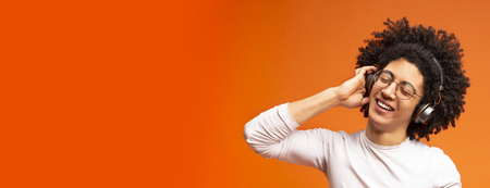 Young black guy relaxing and listening to music using wireless headphones on orange background, empty space