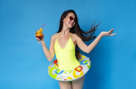 Carefree Girl Enjoying Summer Vacation, Dancing with Tropical Cocktail, Wearing inflatable ring, blue studio background