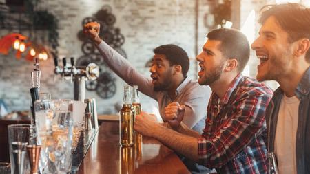 Compañeros viendo el partido de fútbol y animando a su equipo favorito en el Sport Bar, Panorama Foto de archivo