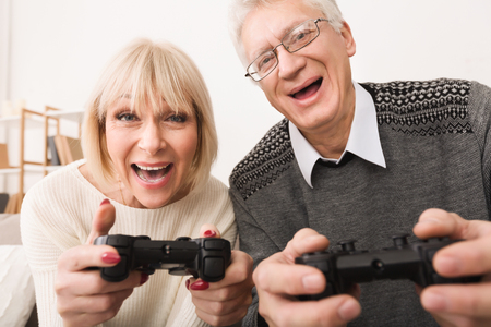 Excited Middle-Aged Couple Playing Video Games With Joystick, Having Fun Together
