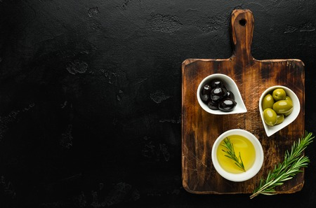 Olive oil and olives in bowls on wooden board over black concrete background, top view, copy space