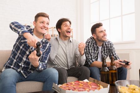Avid Gamers. Friends Playing Video Games And Eating Pizza, Resting At Home