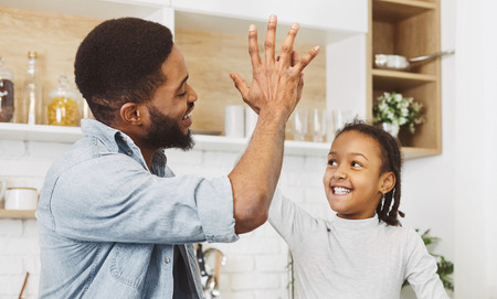 Cute afro child girl giving five to her father at kitchen, copy space. The best father concept