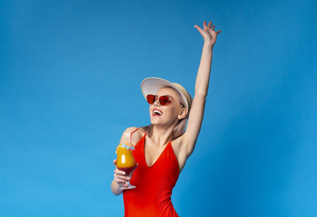 Summer Vacation. Cute Girl in Swimsuit and Sunglasses Enjoying Tropical Cocktail, blue studio background with free space Stockfoto
