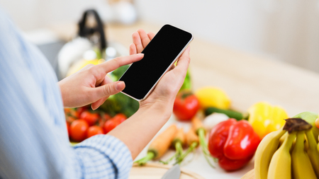 Search Recipe. Woman Using Smartphone Preparing For Cooking Healthy Salad At Home Banque d'images