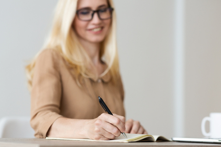 Mature Freelancer Writing Down Plans Project Into Notebook, Focus On Hand
