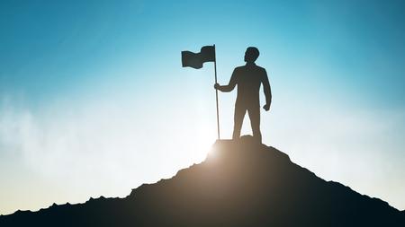 Siluetta dell'uomo con la bandiera sulla cima della montagna sopra il cielo e la luce del sole sullo sfondo