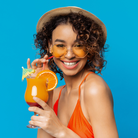 Carefree black girl enjoying fruit non-alcoholic cocktail, blue studio background. Summer time concept Stockfoto