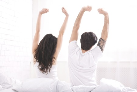Well rested young couple waking up in morning, stretching on bed together, back view, free space