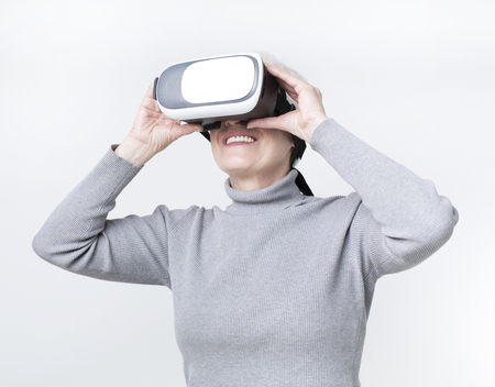 Augmented reality, entertainment and people concept. Senior woman with virtual headset or 3d glasses playing video game, studio shot Stock Photo